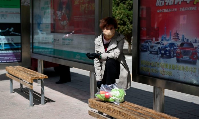 A woman waiting at a bus stop in China. (Wang Zhao/AFP/Getty Images)