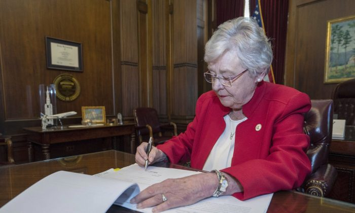 Alabama Gov. Kay Ivey signs a bill that virtually outlaws abortion in the state on May 15, 2019. (Hal Yeager/Alabama Governor's Office via AP)