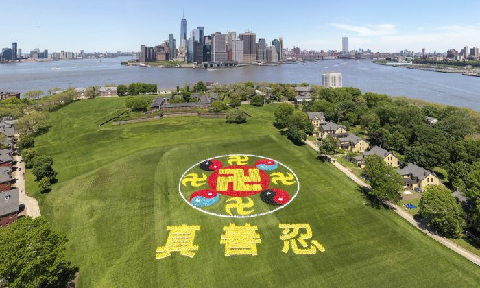 Thousands of Falun Gong practitioners came together on New York City's Governors Island for the character formation event on May 18, 2019. The emblem consists of ancient symbols, the yellow srivatsa symbolizing Buddhism and the red-black and red-blue Taiji symbols representing Taoism. (NTD)