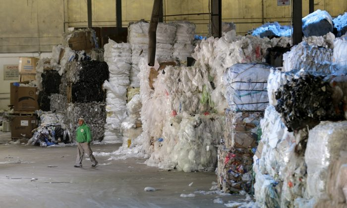 A man walks under towers of recyclables at a GDB International warehouse in Monmouth Junction, N.J. on May 7, 2019. (AP Photo/Seth Wenig)