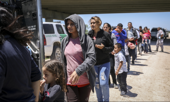 A large group of illegal aliens boards a bus bound for the Border Patrol processing facility after being apprehended by Border Patrol near McAllen, Texas, on April 18, 2019. (Charlotte Cuthbertson/The Epoch Times)