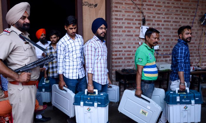 An Indian Punjab Police personnel stands guard as election officials carry Electronic Voting Machines (EVM) and Voter-Verified Paper Audit Trail (VVPAT) leaving a distribution centre in Amritsar on May 18, 2019. (NARINDER NANU/AFP/Getty Images)
