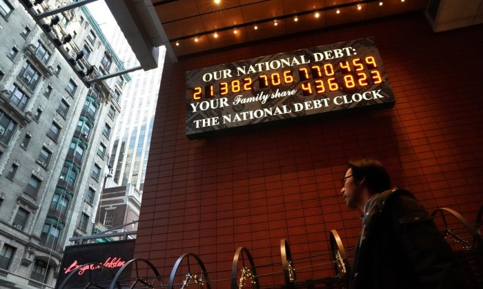 A man walks past the National Debt Clock on 43rd Street in midtown Manhattan, New York City on February 15, 2019. (TIMOTHY A. CLARY/AFP/Getty Images)