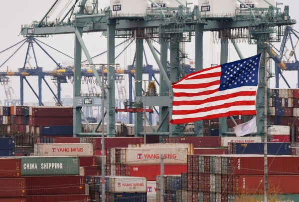Chinese shipping containers beside a US flag at the Port of Los Angeles in Long Beach