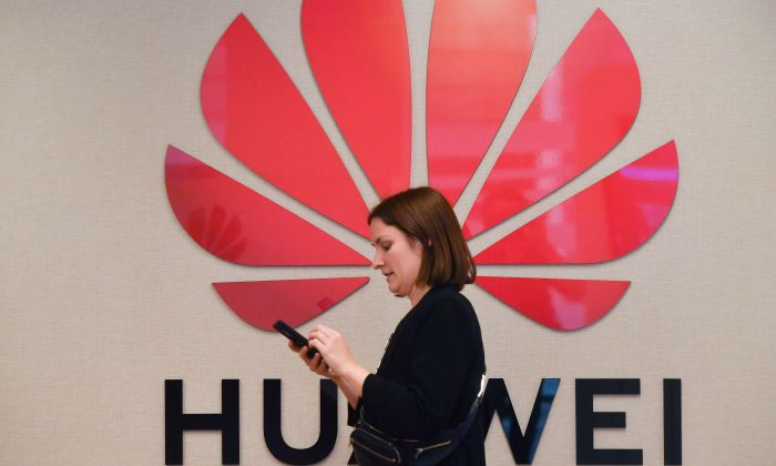 A woman passes by the Huawei logo at the Huawei Cyber Security Transparency Centre in Brussels on May 21, 2019. (EMMANUEL DUNAND/AFP/Getty Images)