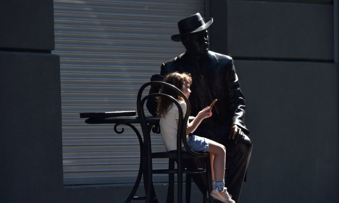 A girl plays with a smartphone as she sits on a monument in the center of Ukrainian capital of Kiev on March 23, 2019. SERGEI SUPINSKY/AFP/Getty Images