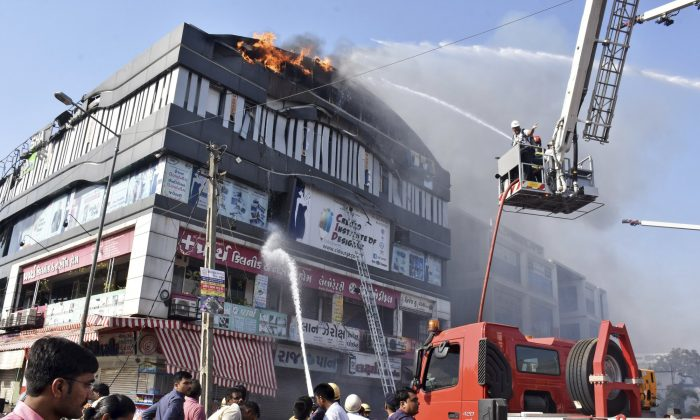 Firefighters work to douse flames on a building in Surat, in the western Indian state of Gujarat on May 24, 2019. (Sarju Parekh/Photo via AP)
