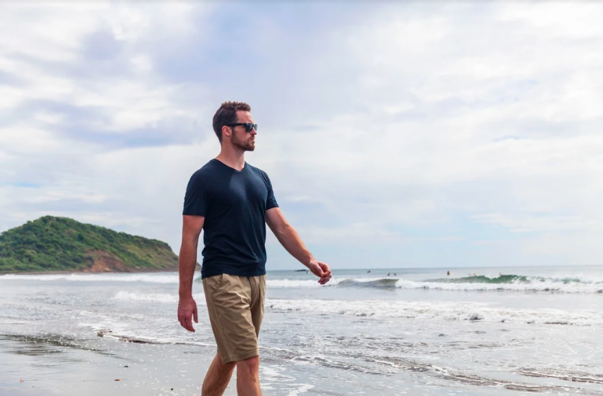 man walking on beach with wool shirt