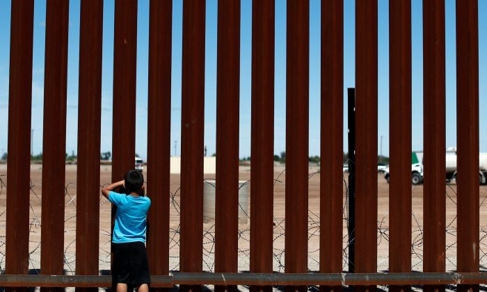 A child looks through the border wall during the visit of U.S. President Donald Trump to Calexico, California, as seen in Mexicali, Mexico, on April 5, 2019. (Reuters/Carlos Jasso)