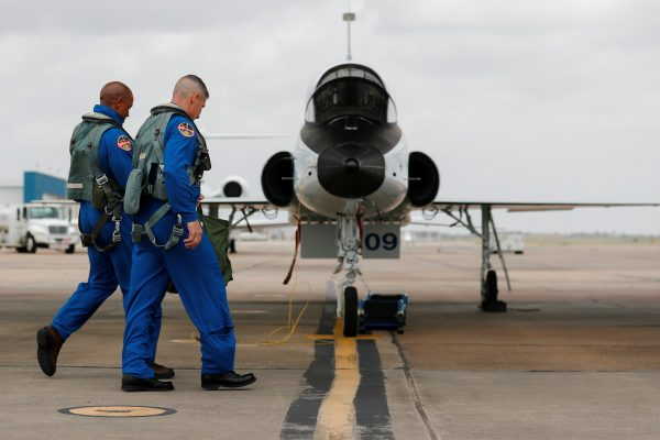 NASA commercial crew astronauts Victor Glover and Michael Hopkins walk out to their aircraft prior to a training flight in Houston, Texas