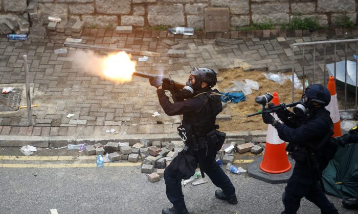 Police officer fires tear gas at protesters during a demonstration against a proposed extradition bill in Hong Kong, China, on June 12, 2019. (Thomas Peter/Reuters)
