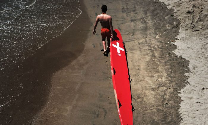 In this file image, a lifeguard walks the beach at Coney Island with a rescue board in the Brooklyn borough of New York City on July 5, 2018. (Spencer Platt/Getty Images)
