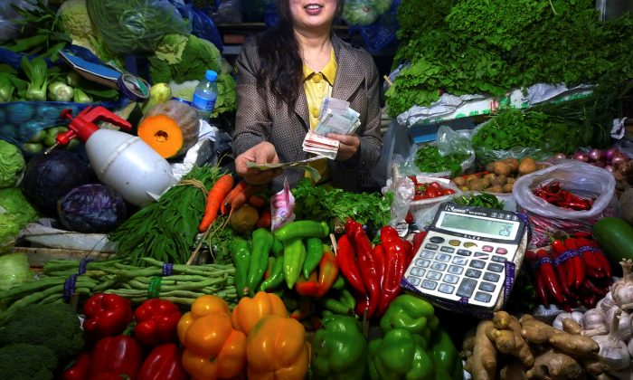 A fruit and vegetable stall owner uses a calculator to work out prices for a customer at a small market in central Beijing on July 7, 2011. (David Gray/Reuters)