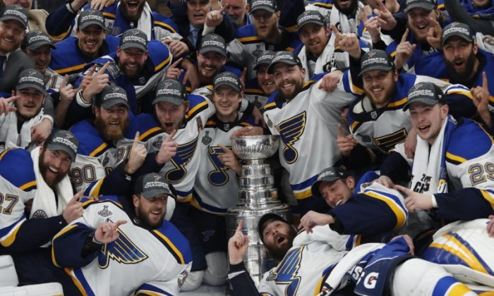 1ec9c0d564d St. Louis Blues players pose for a team photo with the Stanley Cup after  defeating