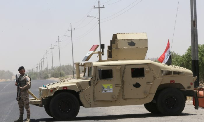 An Iraqi soldier stands next to a military vehicle at the entry of Zubair oilfield after a rocket struck the site of residential and operations headquarters of several oil companies at Burjesia area, in Basra, Iraq, on June 19, 2019. (Essam Al-Sudani/Reuters)