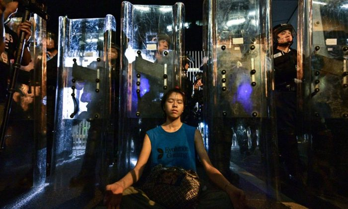Lam Ka Lo (C) meditates in front of a line of riot police standing guard with their shields outside the government headquarters in Hong Kong early on June 12, 2019. (Anthony Wallace/AFP/Getty Images)