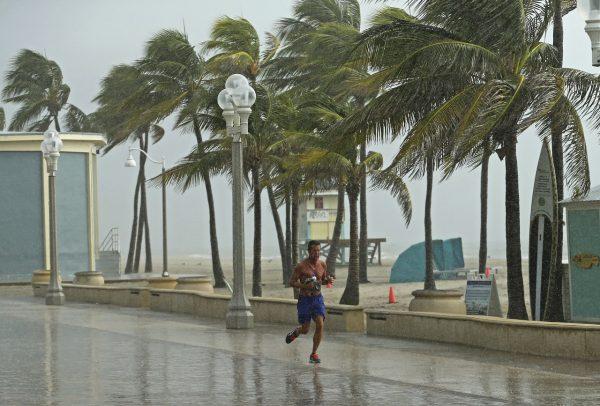 A beachgoer runs under the rain