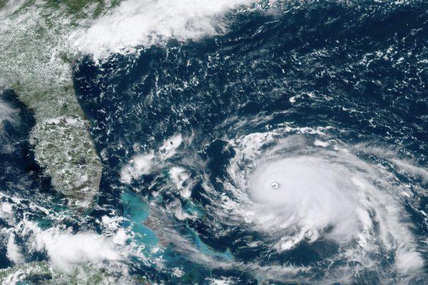 Hurricane Dorian, right, churning over the Atlantic Ocean,