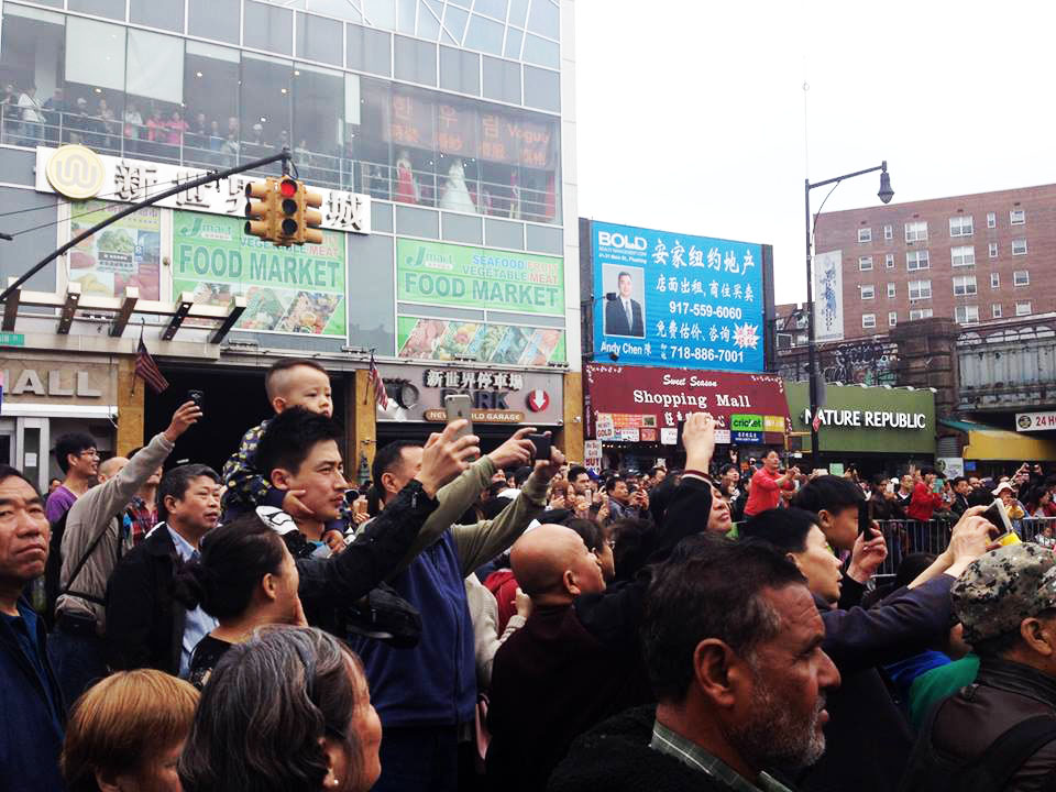 Flushing locals watch and record video of the April 23 parade. (Leo Timm/Epoch Times)