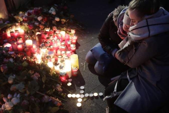 Two women mourn beside candles in Berlin, Germany on Dec. 20, 2016. (AP Photo/Markus Schreiber)