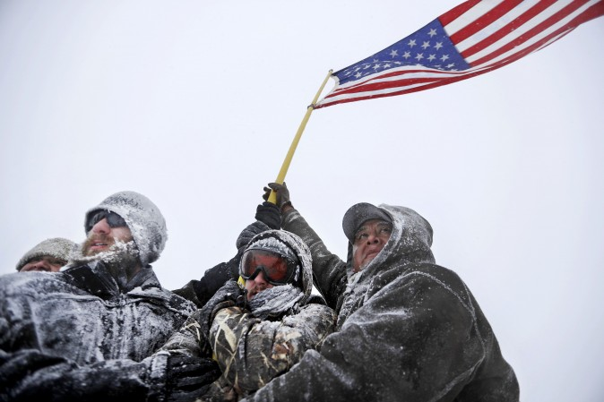 Military veterans huddle together holding a U.S. flag against strong winds during a march outside the Sacred Stone Camp, where people have gathered to protest the Dakota Access Pipeline, near Cannon Ball, N.D., on Dec. 5. (AP Photo/David Goldman)