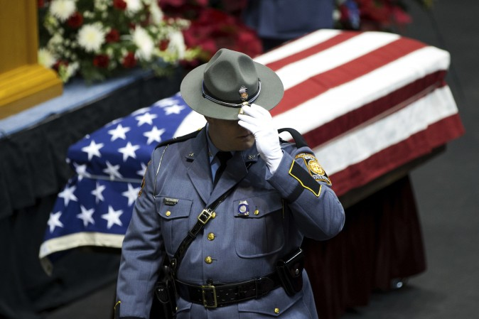 A Georgia State Trooper pay his respects to Americus Police Officer Nicholas Smarr on Dec. 11, who was killed after responding to a domestic disturbance call in Americus, Ga. (AP Photo/Branden Camp)