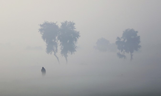 A farmer walks on his field enveloped by thick fog near Hisar, India, on Dec. 23, 2016. (AP Photo/Altaf Qadri)