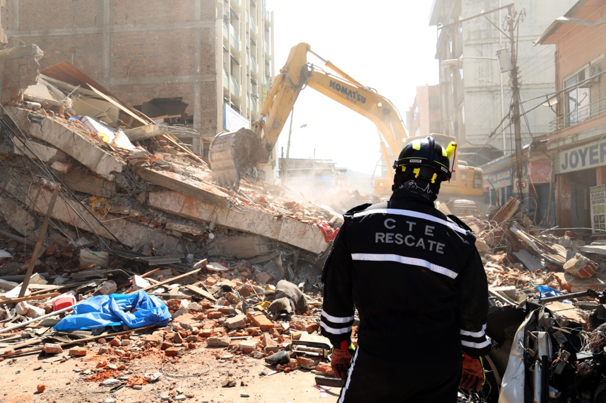 A rescue worker looks as heavy machinery removes the debris of a collapsed building in Portoviejo, Ecuador, Sunday April 17, 2016. A magnitude-7.8 quake, the strongest since 1979, hit Ecuador flattening buildings, buckling highways along its Pacific coast and killing hundreds. (AP Photo/Carlos Sacoto)