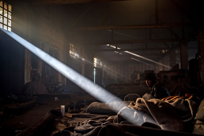 A migrant sits in a makeshift shelter at an abandoned warehouse in Belgrade, Serbia, on Dec. 8, 2016. According to the latest figures, 6,300 migrants are stranded in Serbia. (Andrej Isakovic/AFP/Getty Images)