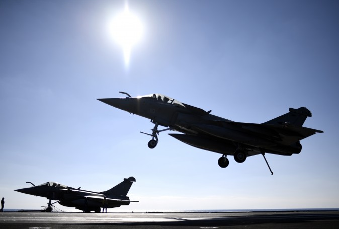 A French Rafale fighter jet lands on the deck of France's aircraft carrier Charles-de-Gaulle operating in the eastern Mediterranean Sea on Dec. 9, as part of an international coalition against the ISIS. (STEPHANE DE SAKUTIN/AFP/Getty Images)