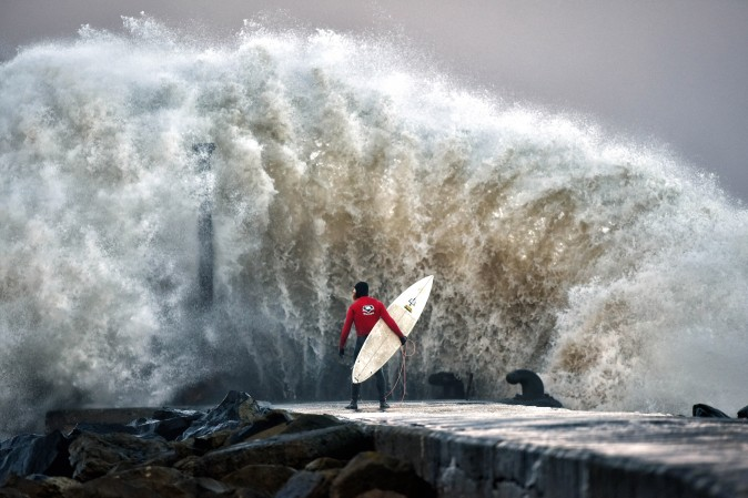 A huge wave crashes against Castlerock pier as professional surfer Al Mennie waits on a break in the swell on in Coleraine, Ireland, on Dec. 22. Storm Barbara is expected to cause major travel disruption when it hits northern parts of the UK later with 90mph winds predicted. (Charles McQuillan/Getty Images)