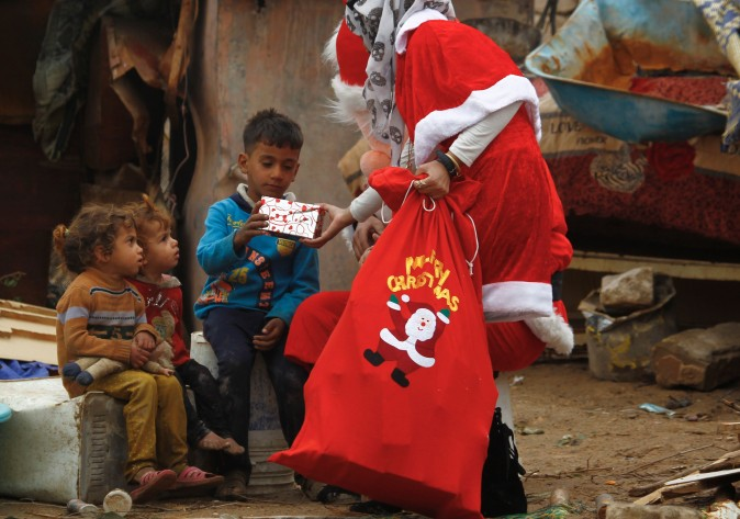 An odontology student dressed in a Santa Claus outfit distributes gifts to impoverished children outside their shanty home in Najaf, Iraq, on Dec. 25, 2016. (Haidar Hamdani/AFP/Getty Images)