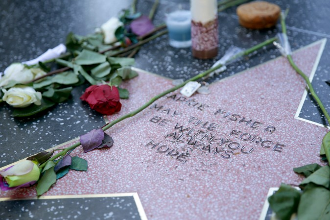 """Carrie Fisher is remembered with a makeshift star on the Hollywood Walk of Fame in Hollywood, Calif., on Dec. 28. The star was reportedly made by a fan who added Fisher's name to a blank star along with the words """"may the force be with you always"""" and """"hope."""" Fisher was never nominated for a star while living and now won't be eligible until the fifth anniversary of her death. (Greg Doherty/Getty Images)"""