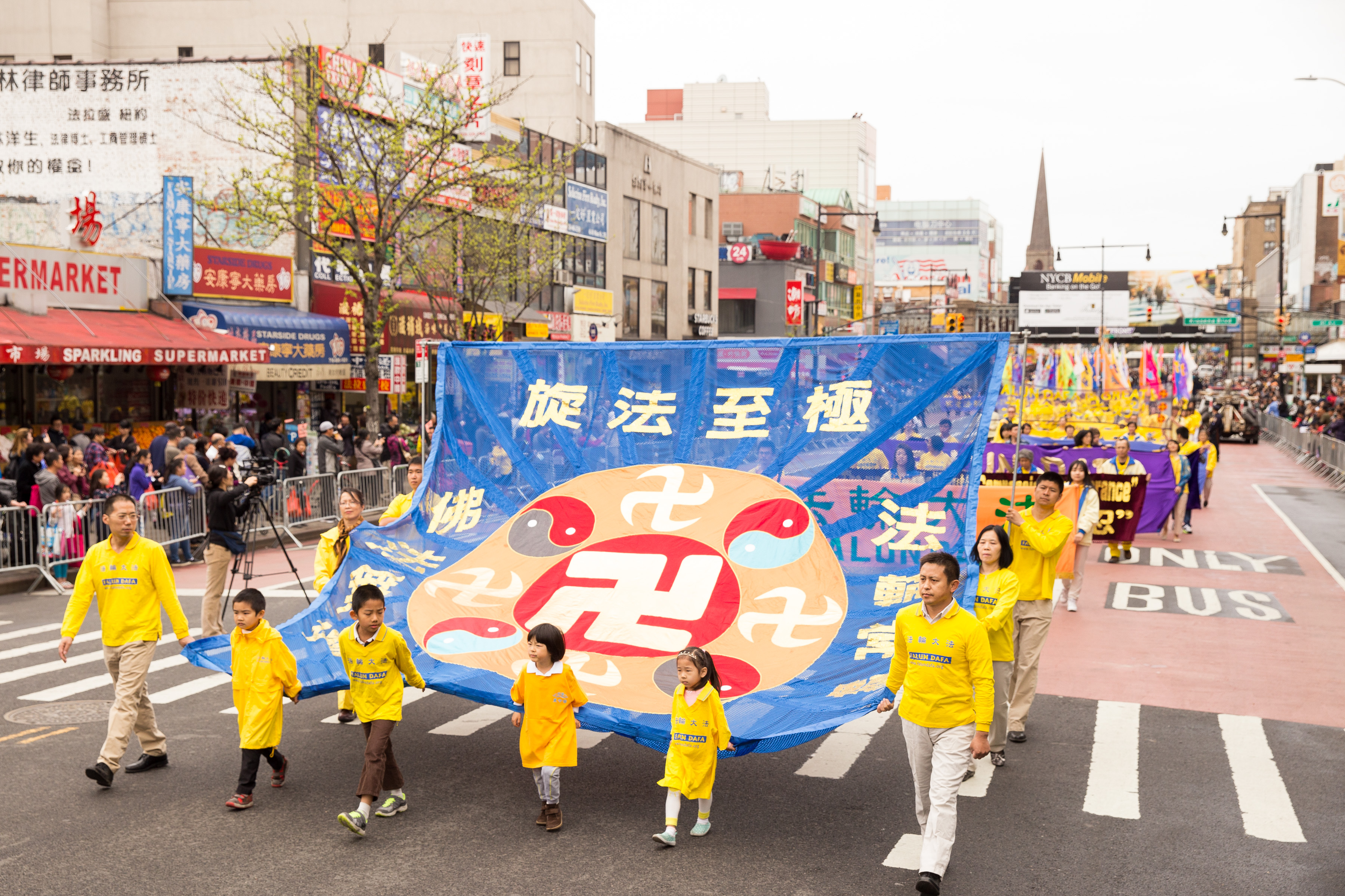 Falun Gong practitioners participating in the Flushing parade hold a large banner showing the Law Wheel symbol of Falun Gong. (Larry Dye/Epoch Times)