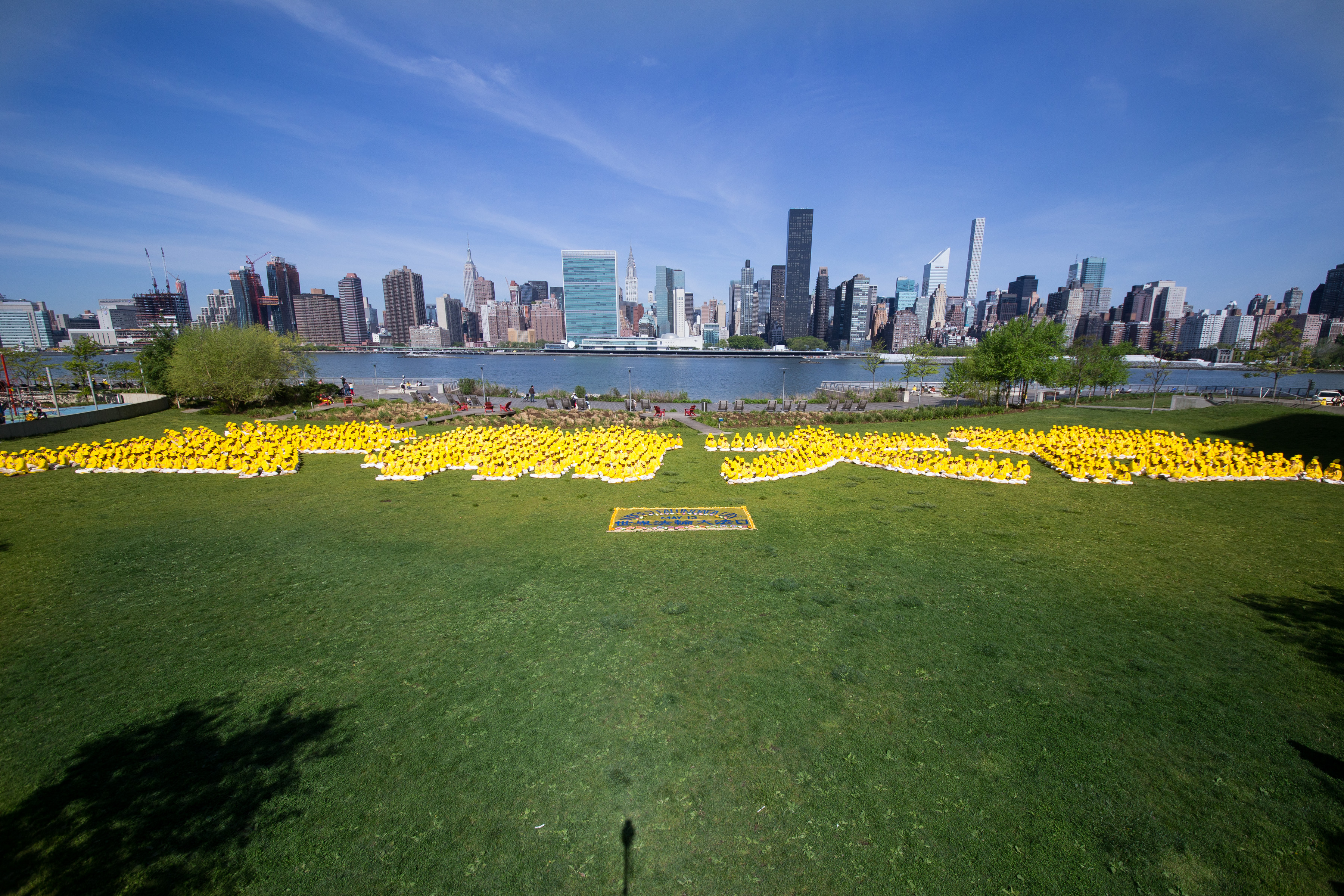"Over a thousand Falun Gong practitioners from New York, Taiwan, and other Asian countries form the Chinese characters for ""Falun Dafa"" at Gantry Plaza State Park on May 12, 2016. (Larry Dye/Epoch Times)"