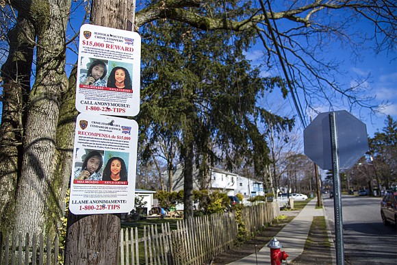 Signs offering a reward for information regarding the murders of Nisa Mickens (L) and Kayla Cuevas are posted near Brentwood High School, where they studied, in Suffolk County, N.Y., on March 29. (Samira Bouaou/The Epoch Times)
