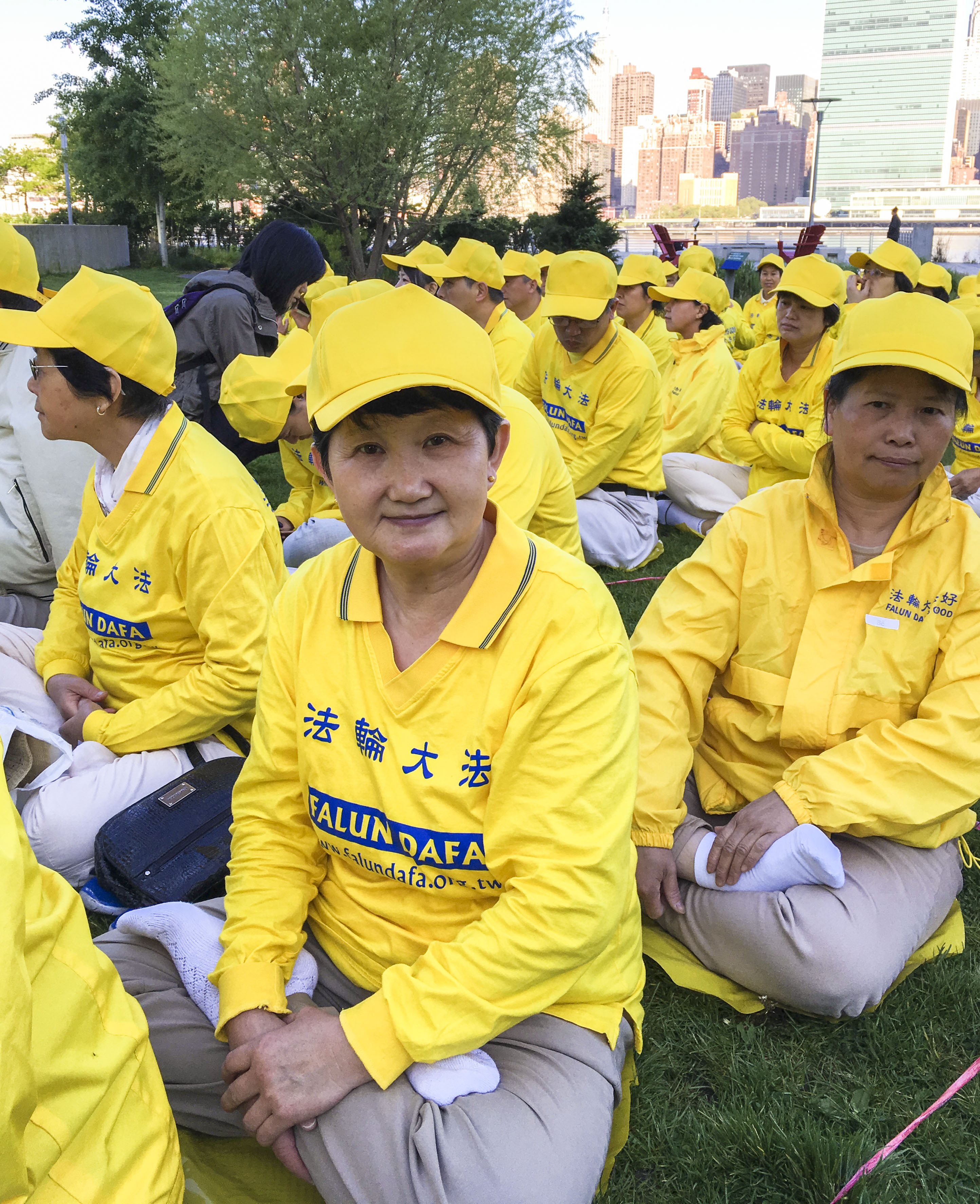 Zhang Guanghua (C), a Falun Gong practitioner from Beijing, joins a character formation event at Gantry Plaza State Park on May 12, 2016. (Larry Ong/Epoch Times)