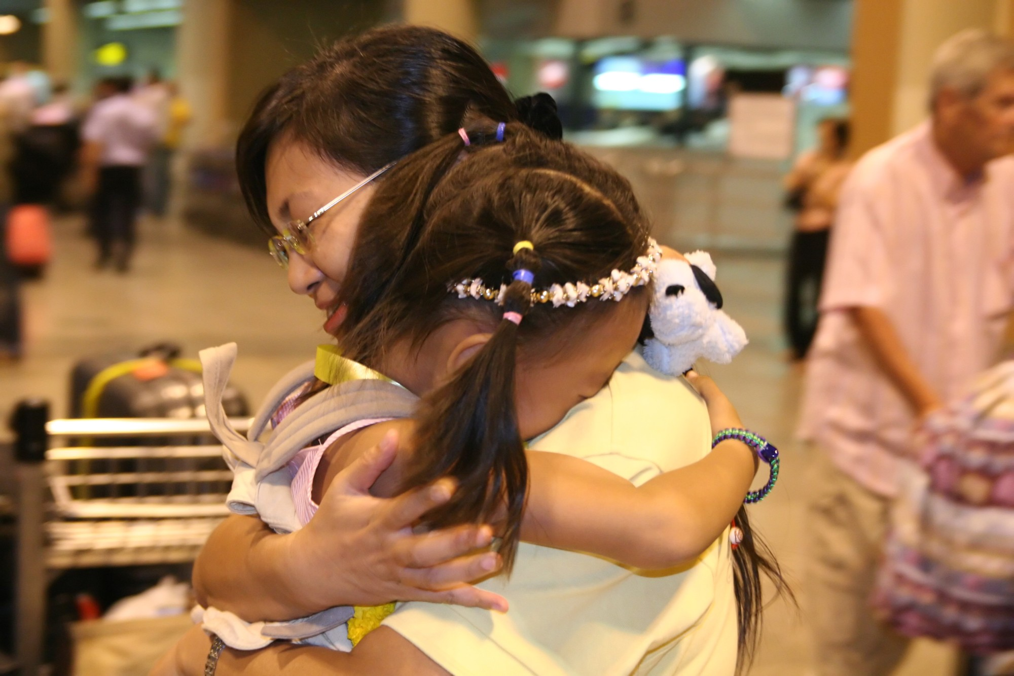 TOGETHER AT LAST: Miao Miao and her 6-year-old daughter Hua Yuchen share a touching moment at Don Muang International Airport in Bangkok on January 23, 2006. They were separated after Miao was imprisoned at the Bangkok Immigration Detension Center following an arrest that many believe was illegal. They flew to asylum in Norway early morning on the 24th. (The Epoch Times)